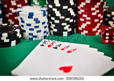 full house and poker chips on green table