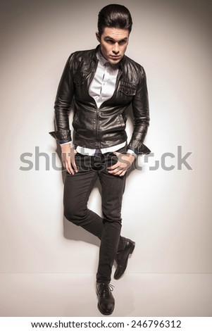 Full legth picture of a young fashion man holding his thumbs in pockets while leaning on a white wall, looking away from the camera. - stock photo