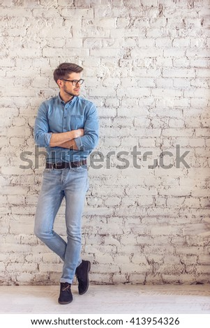Full lenght portrait of handsome young man in jeans clothes and eyeglasses looking away and smiling, standing against white brick wall - stock photo