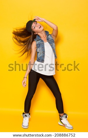 full lenght Portrait of pretty young woman in casual wear against yellow background - stock photo