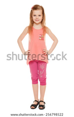 Full length a cheerful little girl in shorts and a T-shirt; isolated on the white background - stock photo