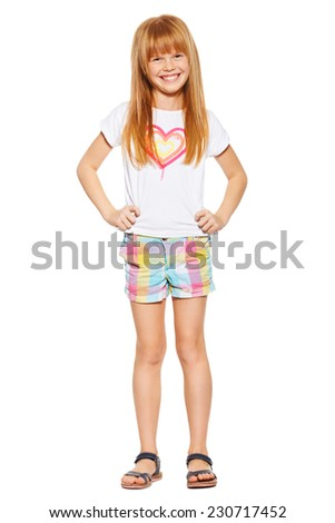 Full length a cheerful little girl with red hair in shorts and a T-shirt; isolated on the white background - stock photo