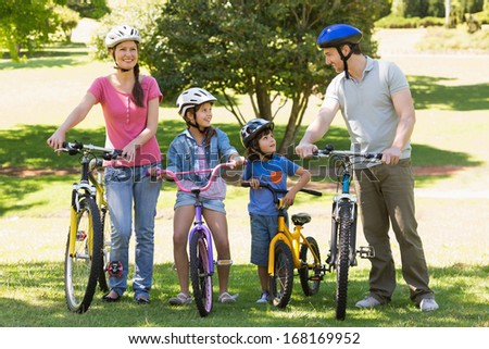 Full length a family of four with bicycles in the park - stock photo