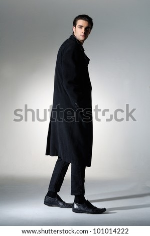 Full length a young fashion male walking on light background