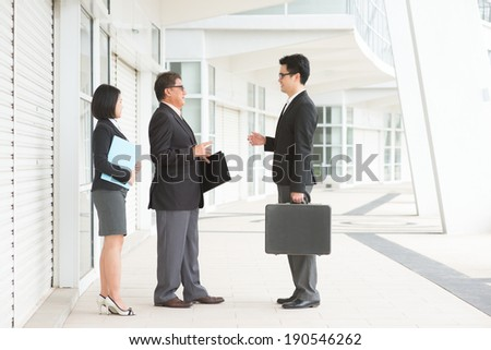 Full length Asian business team meeting, having discussion over office. - stock photo