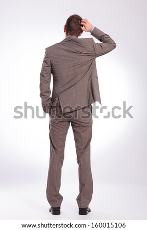 full length back view picture of a young business man scratching his head while holding a hand in his pocket. on a gray background - stock photo