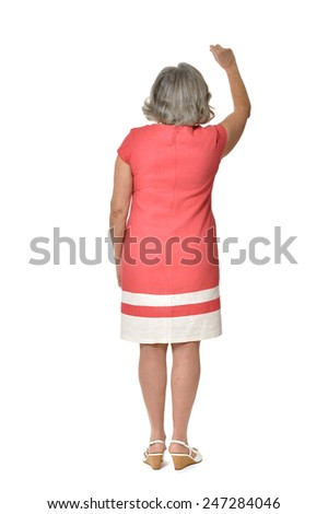 Full length back view portrait of senior woman in red dress pointing on white background