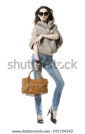 full-length beautiful woman in sunglasses with handbag posing  - stock photo