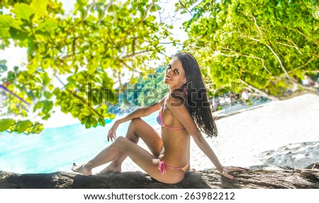 Full length body young adult erotic girl sit on tropical tree old trunk texture Cute woman against beach island ocean or sea Female wear colorful swimsuit against summer coast with people tourist - stock photo