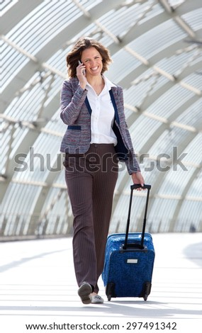 Full length business woman walking at station with bag and mobile phone - stock photo