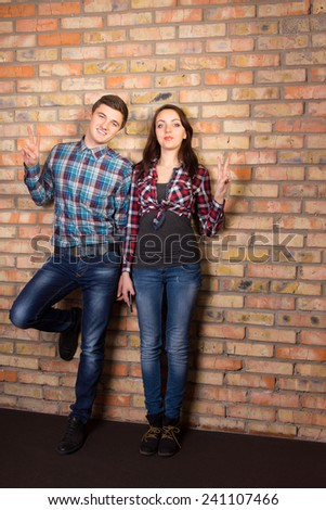 Full Length Capture of Young White Couple in Casual Outfit Leaning on Brick Wall While Looking at the Camera. - stock photo