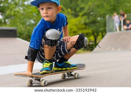 Full Length Close Up of Serious Young Boy Crouching on Skateboard in Skate Park with Other Skaters in Background on Ramp - stock photo