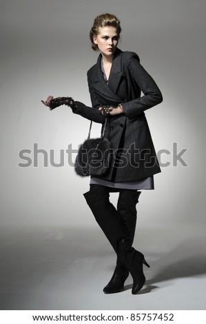 full-length fashion girl with handbag posing on light background - stock photo