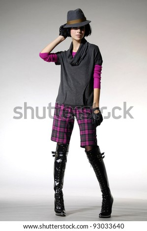 full-length fashion model in fashion boots posing on gray background - stock photo