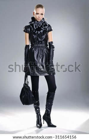full-length fashion model in groves clothes holding handbag posing  - stock photo