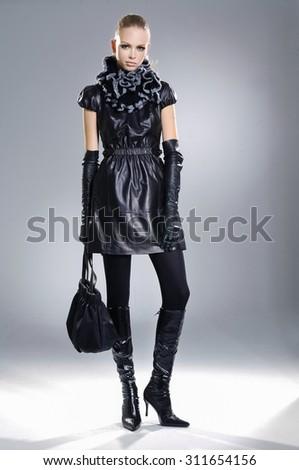 full-length fashion model in groves clothes holding handbag posing  - stock photo