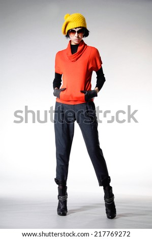 full-length fashion photo of young woman in sunglasses with gloves posing on light background  - stock photo