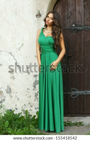 full length fashion portrait of young elegant woman standing near old stone wall and wooden door in long green dress           - stock photo