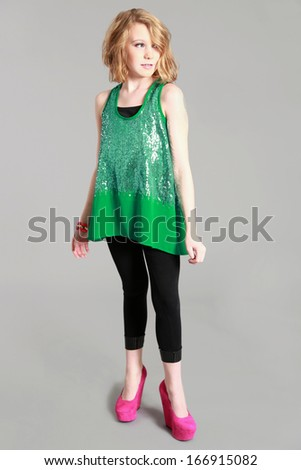 full length fashion shot of beautiful preteen girl looking away from camera - stock photo