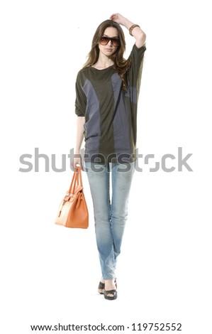 Full length fashion young women wearing sunglasses with bag walking - stock photo