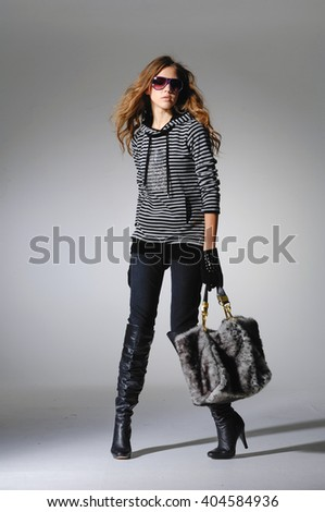 Full length fashionable woman in sunglasses holding bag posing in light background