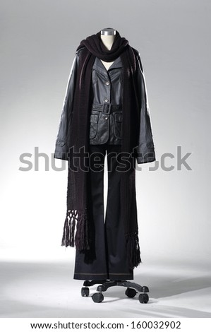 full-length female clothes in scarf on a mannequin in light background