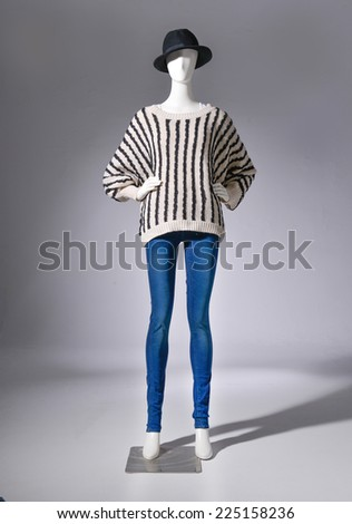 full-length female clothing in jeans with cap on mannequin on gray background - stock photo