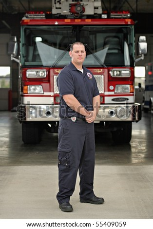 full-length fireman standing in front of fire engine at firehouse wearing blue uniform and serious face - stock photo