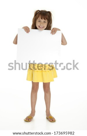 Full length front view of cute little girl holding blank sign on white background. - stock photo
