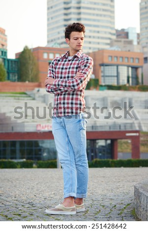 Full length handsome man, fashion model, with toupee posing outdoors in summertime over city background - stock photo