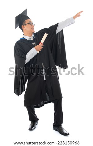 Full length happy pan Asian university student in graduation gown, standing isolated on white background. - stock photo