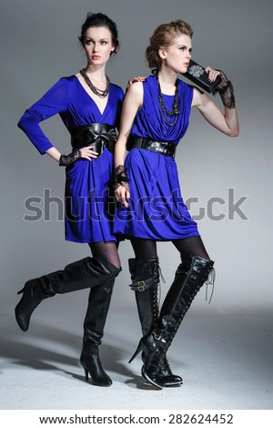 full-length high young stylish two model in fashion blue dress posing in the studio  - stock photo
