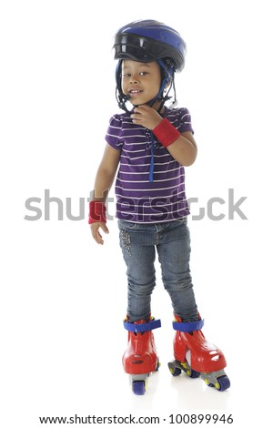 Full-length image of a preschooler tightening her helmet as she prepares to roller blade.  On a white background.