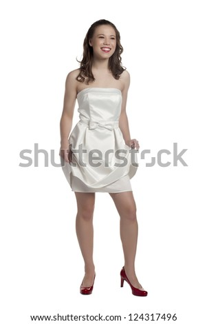 Full length image of a young female holding her white dress as she smiles - stock photo