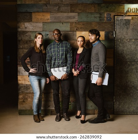 Full length image of multiracial creative team posing for camera in office. Young business people standing together against a wooden wall. - stock photo