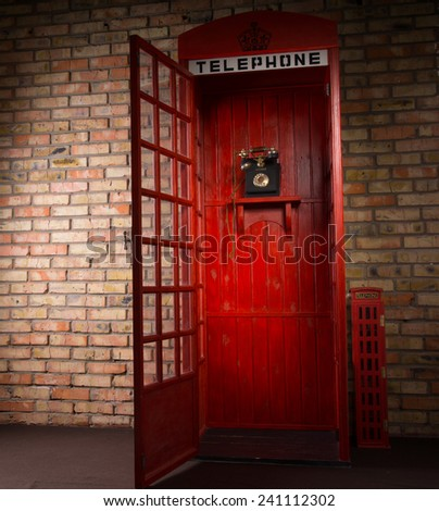 Full Length Image of Red Public Telephone Booth with Old Fashioned Telephone and Open Door - stock photo