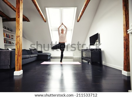 Full length image of young caucasian woman practicing yoga exercise at home. Fit young woman standing on one leg and meditating in her living room. - stock photo