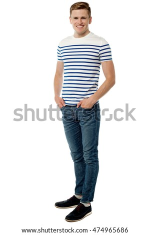 Full length image young man posing with hands in pockets.