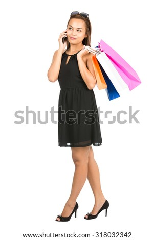 Full length isolated on white profile of trendy Asian female shopper hanging out talking casually on her mobile phone with colorful department store bags in a stylish black dress, sunglasses V