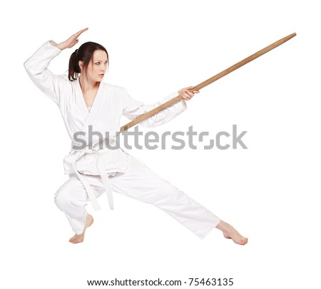 full-length isolated portrait of beautiful martial arts girl in kimono excercising karate kata wit staff