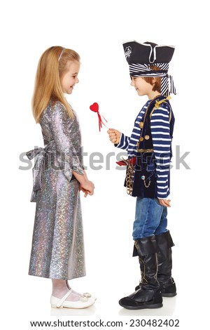 Full length little boy wearing pirate costume presenting small heart shape to his lady, over white background - stock photo