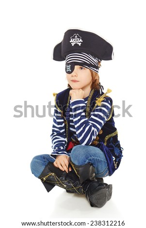 Full length little boy wearing pirate costume sitting on the white studio floor thinking looking up to the blank space, over white background - stock photo