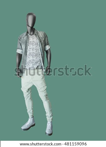 Full length male mannequin dressed in shirt, t-shirt and jeans, isolated on green background. No brand names or copyright objects.