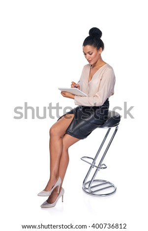 Full length mixed race african american - caucasian business woman sitting on the chair and making notes in a book - stock photo