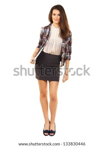 Full length of a beautiful college student with laptop standing against the white background