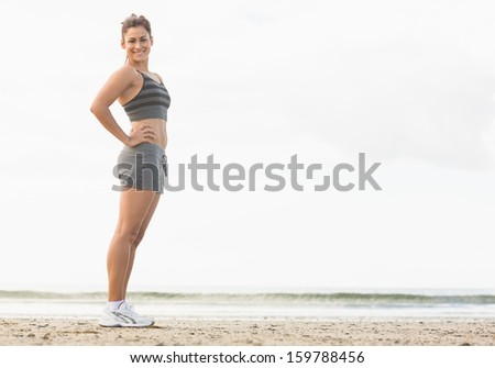 Full length of a beautiful slender woman posing with her hands on hips on the beach - stock photo