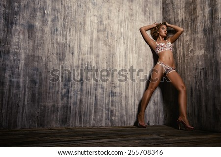 Full length of a beautiful slender young woman alluring in sexual lingerie.  - stock photo