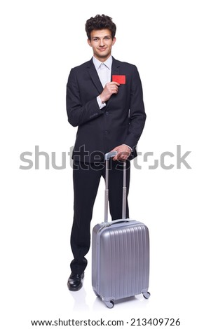 Full length of a businessman standing with a luggage, showing blank credit card, over white background - stock photo