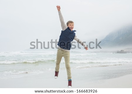 Full length of a casual young boy jumping at the beach