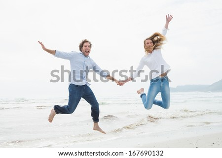 Full length of a cheerful young couple holding hands and jumping at the beach - stock photo